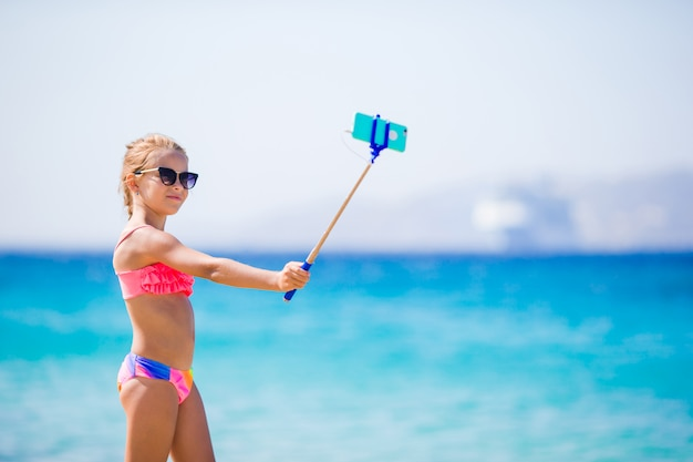Meisje dat zelfportret neemt door haar smartphone op het strand. kind geniet van haar suumer vakantie en maakt foto's ter herinnering