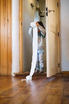 Meisje dat zich binnen het toiletpapier van de badkamersholding bevindt
