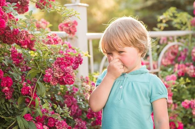 Meisje dat zich dichtbij de rozenstruiken bevindt. het concept van allergie