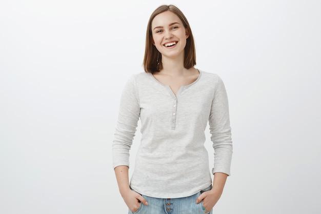 Meisje dat zich gelukkig voelt als tiener en een zorgeloos leven leidt. portret van gezellige vriendelijk ogende charmante vrouwelijke brunette hand in hand in zakken terloops en glimlachend vreugdevol