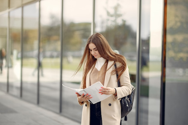 Meisje dat zich in een de lentestad bevindt en documenten in haar hand houdt