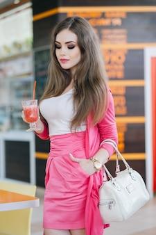 Meisje dat zich met een soda met stro in een hand