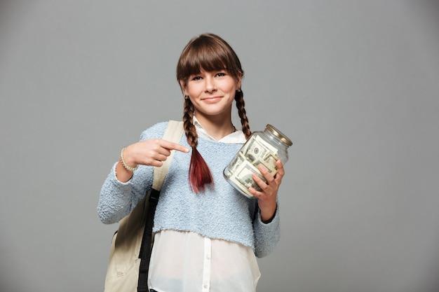 Meisje dat zich met kruikhoogtepunt bevindt van geld