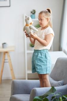Meisje dat zich op de leunstoel bevindt en stuk speelgoed in haar handen bekijkt dat zij thuis speelt