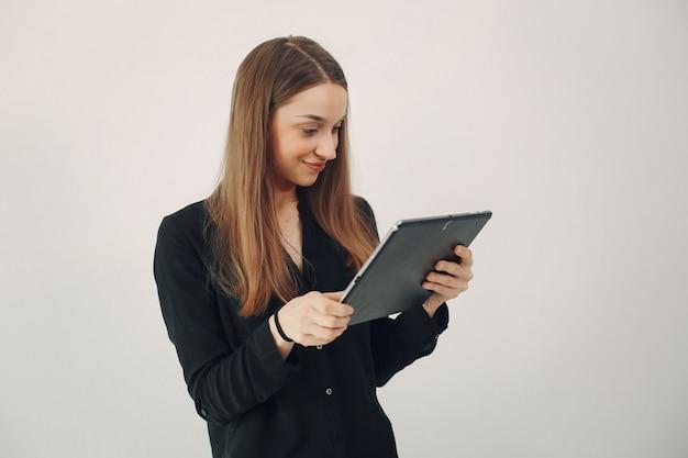 Meisje dat zich op een witte muur met laptop bevindt