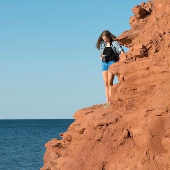 Meisje dat zich op klip bevindt die atlantische oceaan, groene geveltjes, cavendish, prins edward eilanden, ca overziet