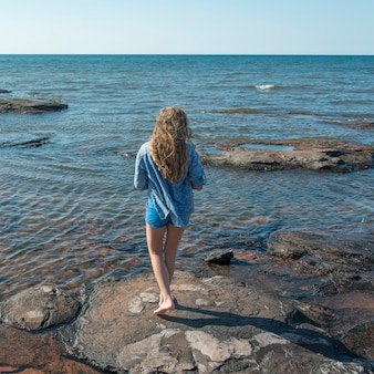 Meisje dat zich op rotsen langs cavendish-strand, groene gallen, prins edward eilanden, canada bevindt