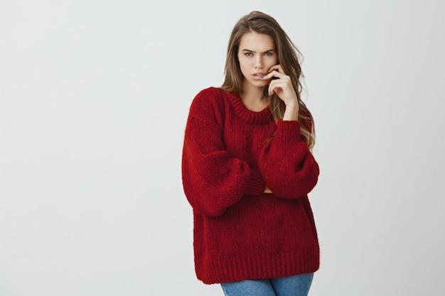 Meisje dat zich op wiskundeles probeert te concentreren. portret van mooie vrouwelijke vrouw in rode losse trui loensen terwijl gericht kijken, hand houden op gezicht, berekeningen maken in gedachten