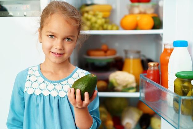 Meisje dat zich voor een koelkast bevindt en voedsel kiest