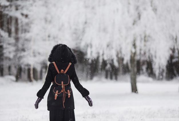 Meisje dat zich voor een mooi de winterbos bevindt, dat tegen het de winterbos wordt gesilhouetteerd, een mens die zich op de sneeuw bevindt