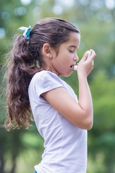 Meisje dat zijn inhaleertoestel gebruikt