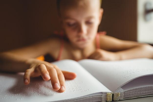 Meisje dat zijn rechterhand gebruikt om braille te lezen