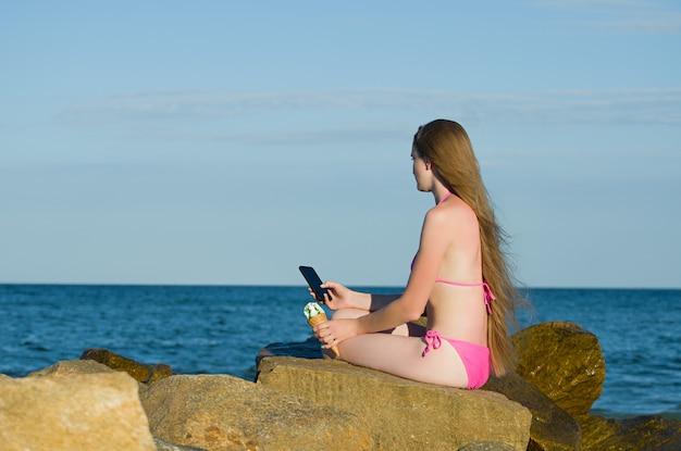Meisje dat zorgvuldig de telefoon, in een badpak op het strand onderzoekt