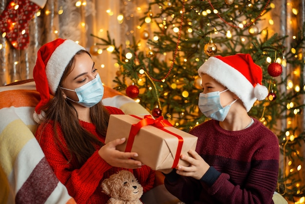 Meisje deelt doosgeschenk met haar jongere broer, beide in medische maskers