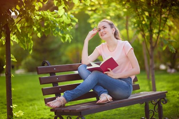 Meisje denkt wat te schrijven in een notitieboekje, zittend in het park
