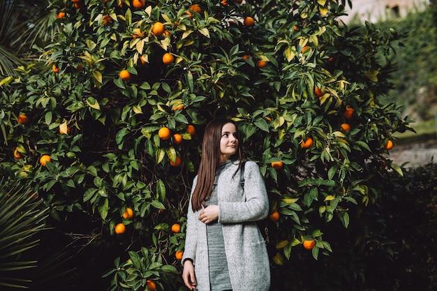 Meisje dichtbij de mandarijnboom. de boom vol fruit