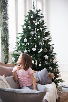 Meisje dichtbij hij kerstboom, wachtend op de kerstman en een wonder