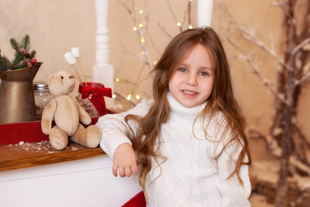 Meisje dichtbij houten kar met kerstmissuikergoed