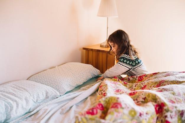 Meisje die bedsheet in slaapkamer schikken