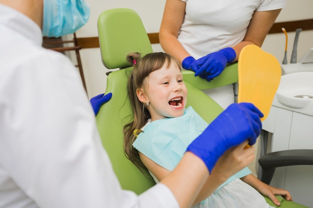 Meisje die bij tandarts in de spiegel kijken