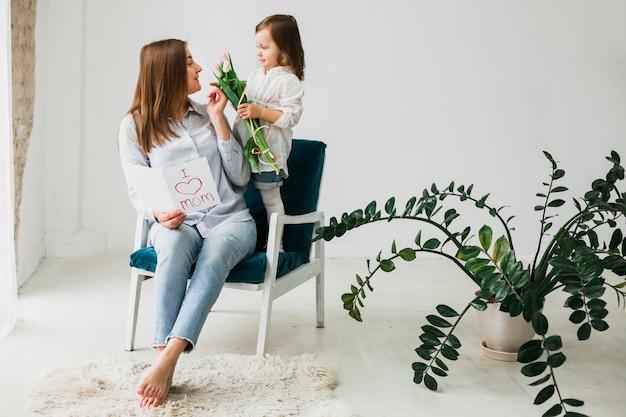 Meisje die bloemen geven aan moeder met groetkaart