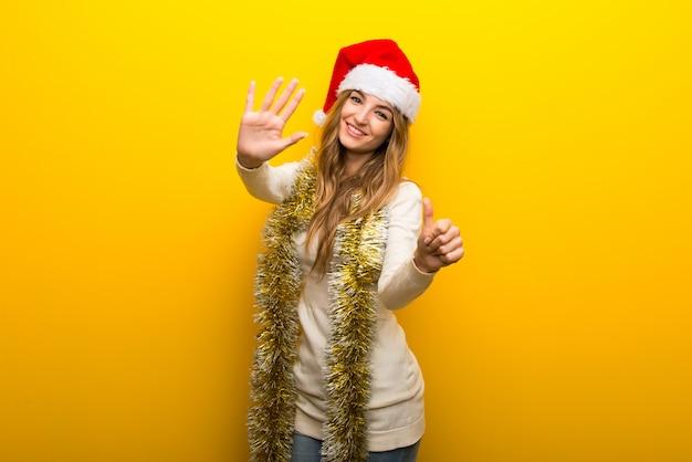 Meisje die de kerstmisvakantie op gele achtergrond vieren