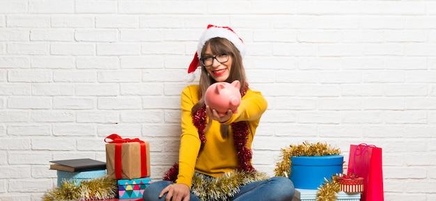 Meisje die de kerstmisvakantie vieren die een grote piggybank houden