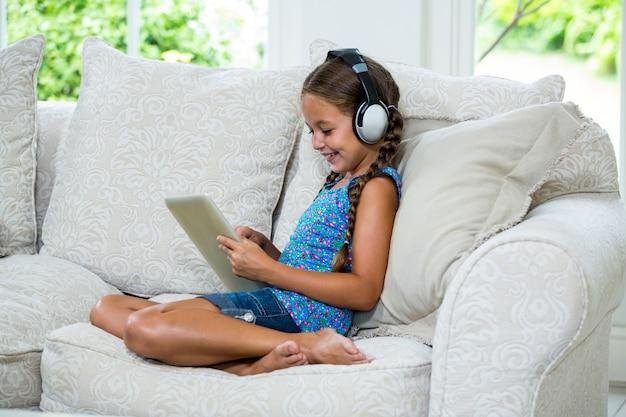 Meisje die digitale tablet gebruiken terwijl het luisteren muziek op bank