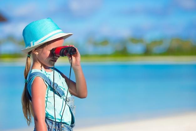 Meisje die door verrekijkers in zonnige dag tijdens de zomervakantie kijken