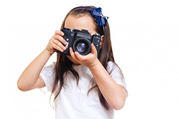 Meisje die een beeld met een professionele retro camera nemen die op wit wordt geïsoleerd