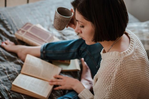 Meisje die een boek lezen en koffie in bedvoeten drinken op de muur.