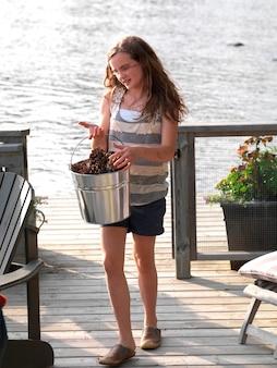 Meisje die een emmer denneappels, meer van het hout, ontario, canada dragen