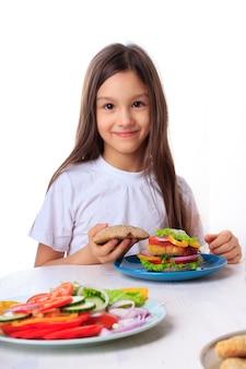 Meisje die een gezonde veganist veggie hamburger met groene salade, whole-whealt bloembroodjes en geïsoleerde kikkererwtenfritters eten