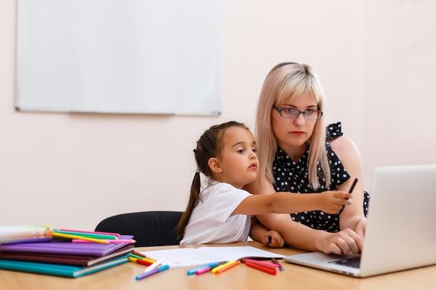 Meisje die een laptop computer op school met behulp van