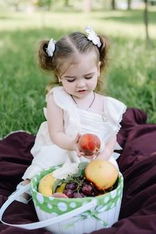 Meisje die een perzik houden en en van zonnige de zomerdag zitten genieten