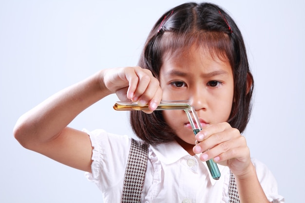 Meisje die een reageerbuis met vloeistof houden, wetenschapsschemie en wetenschapsonderwijs