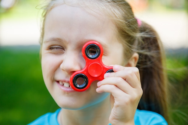 Meisje die een rode fidgetspinner in openlucht houden
