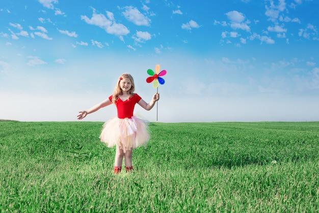 Meisje die een stuk speelgoed bloem op achtergrondhemel en gebied houden