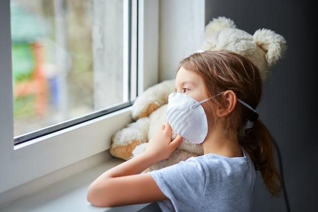 Meisje die en teddybeer in masker dichtbij het venster houden koesteren.