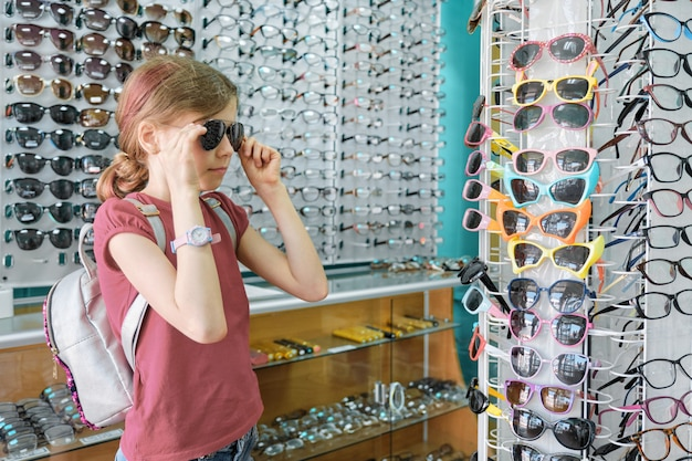 Meisje die en zonnebril, kind dichtbij winkelvenster in eyewear opslag kijken kiezen