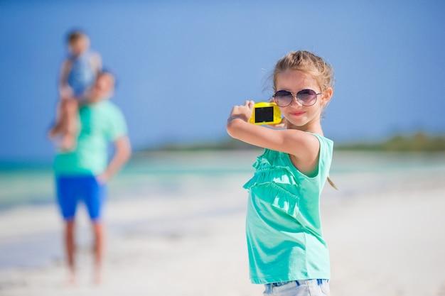Meisje die foto op telefoon van familie maken bij het strand