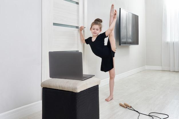 Meisje die gymnastiekoefeningen doen die thuis het online leren met laptop computer gebruiken