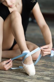 Meisje die haar balletschoenen binden