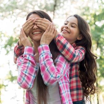 Meisje die haar moederogen behandelen met hand bij park