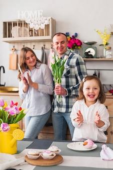 Meisje die handen slaan dichtbij ouders met bloemen