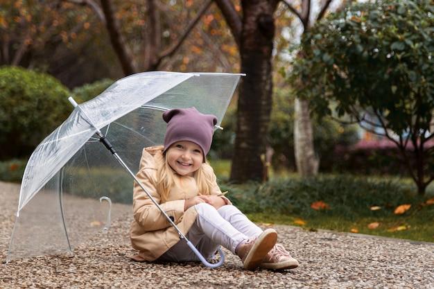 Meisje die in een park onder een paraplu tijdens een regen lopen