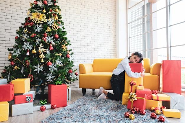 Meisje die kerstboom in woonkamer verfraaien.