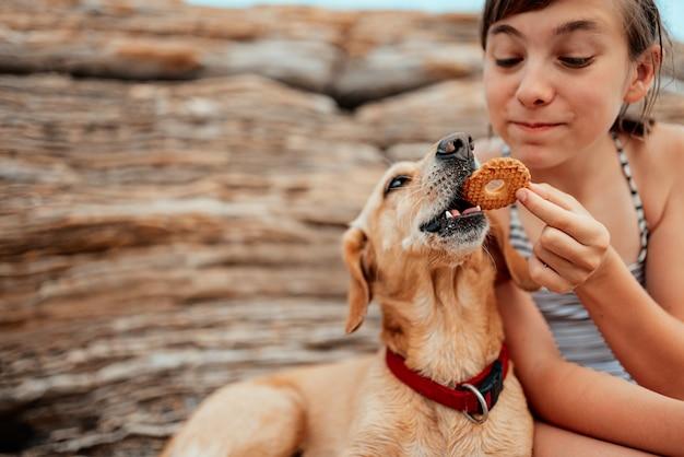 Meisje die koekjes delen met haar hond op het strand