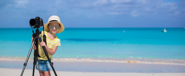 Meisje die met camera op driepoot tijdens haar de zomervakantie schieten