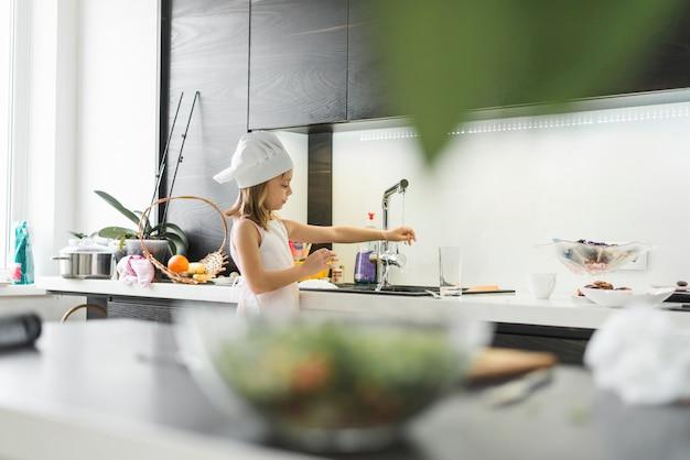 Meisje die met chef-kokhoed haar hand thuis wassen onder tapkraan